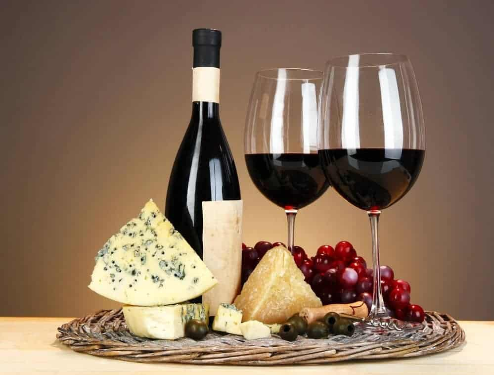 Refined still life of wine, cheese and grapes on wicker tray on wooden table on beige background