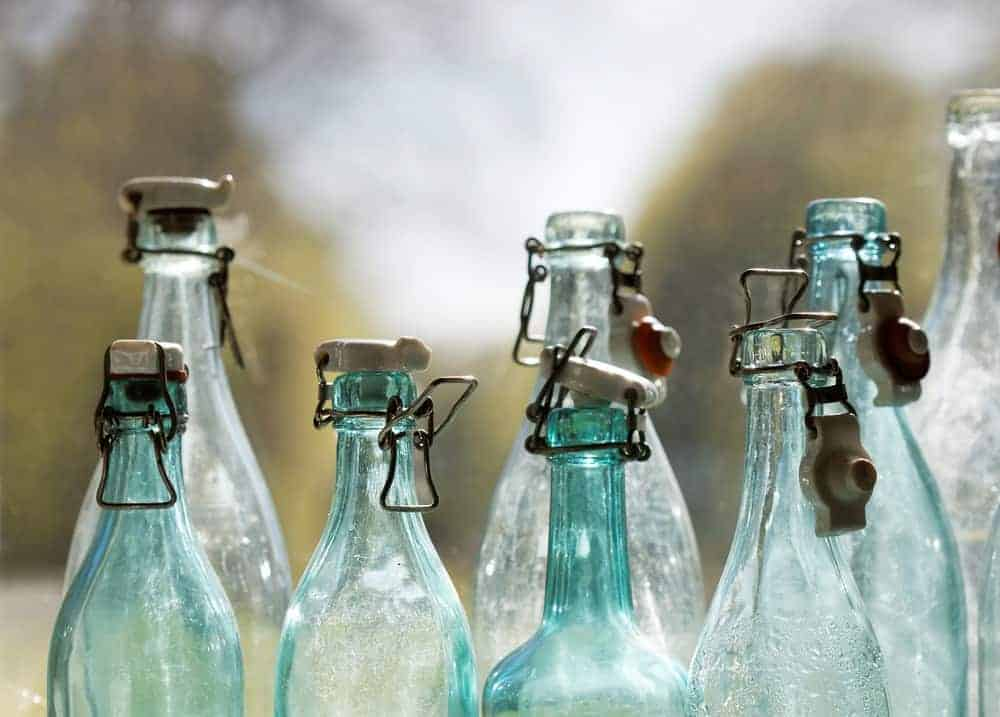 Group of back lit blue and transparent old fashioned empty glass bottles in a window, closeup