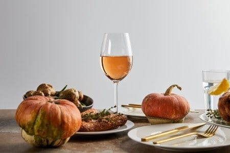Whole pumpkins near baked potatoes and carrots, and glasses with rose wine and lemon water isolated on grey